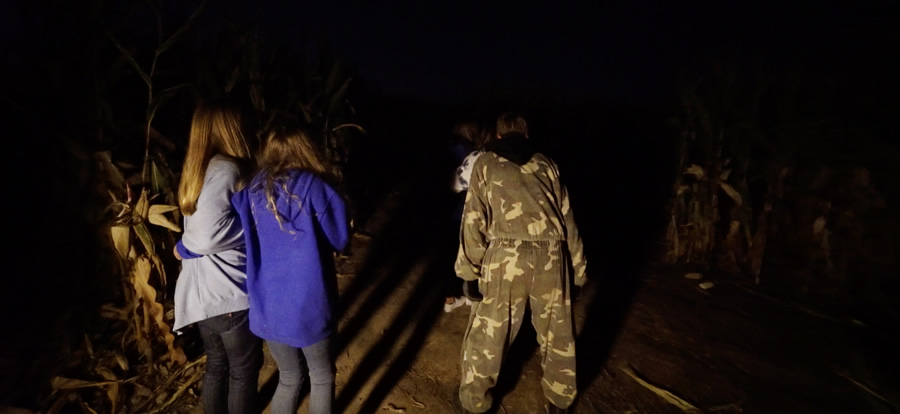 Patrons get scared in a dark corn maze attraction at Hanna Haunted Acres